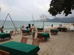 Buri Rasa Village Hotel setting up chairs and tables on the beach for food